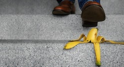 Accident in Daily Life Concept. Man Stepping Down Stair on a Banana Peel. Insurance or Business Metaphor