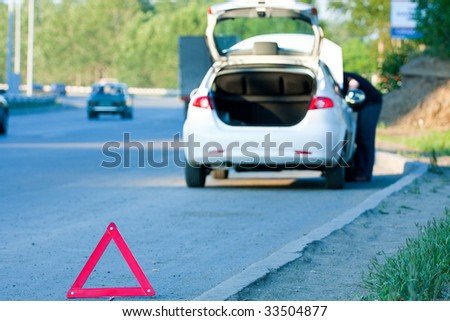 Accident on a road. Focus is on the red triangle sign