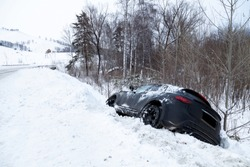 Accident on a winter snowy track with a black car skidding and falling into a ditch due to ice. Safety and poor driving on the road.
