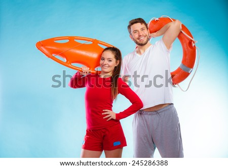 Accident prevention and water rescue. Young man and woman lifeguard couple on duty holding buoy lifesaver equipment on blue Сток-фото ©