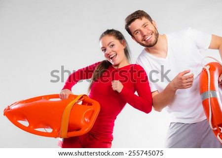 Accident prevention and water rescue. Young man and woman lifeguard couple on duty holding ring buoy float lifesaver equipment having fun on gray Сток-фото ©