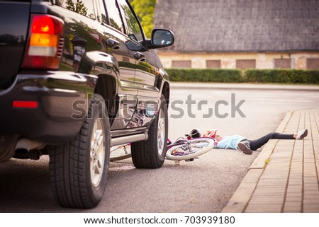 Accident. Small girl on the bicycle is hit by the car #703939180