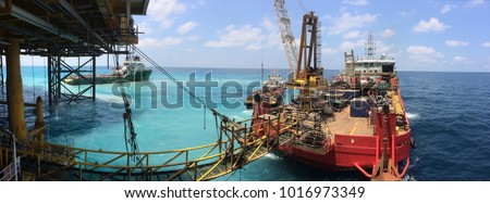 Accommodation work barge transfers personnel to crew boat during simultaneous operations with jack up rig at wellhead platform. #1016973349