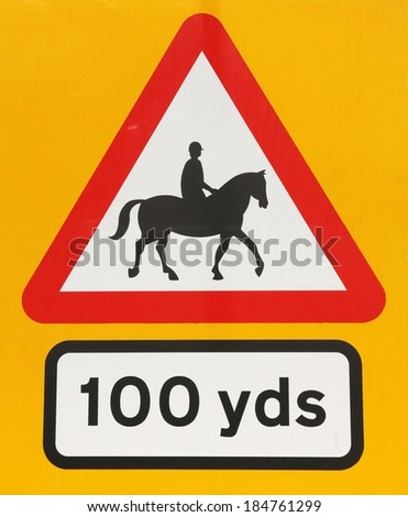 Accompanied horses or ponies, British road warning sign on a yellow background.  #184761299