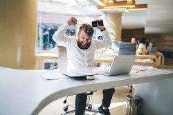 Accomplished male raising hands while celebrating completed startup project happy with received earning and new opportunity, satisfied businessman with cellphone gadget rejoicing at table desktop