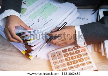 Accountant Business woman Manager checking and signing applicant filling documents reports papers company application form near calculator on desk office. Document Report and business busy Concept #1131062681