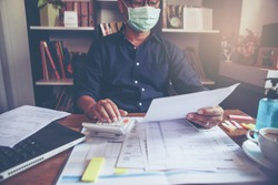 Accountant calculate tax return and work online at home, Asian businessman wear a mask, plan budget and account balance sheet and personal income for worker have income under us law.