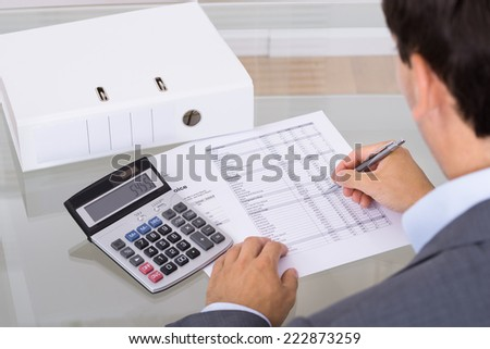 Accountant calculating finances. Over the shoulder view
