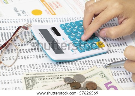 Accountant Checking A Spreadsheet With Calculator and dollars.