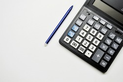 Accountant's Day. Calculator and pen on white background with copy space.