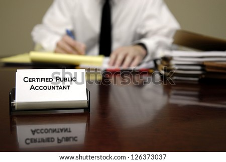 Accountant sitting at desk with stacks of files and business card