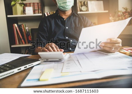 Accountant wear mask work annual budget with a calculator. Work from home, Calendar 2019 and personal income tax form for who have income under US law placed on desk. Annual Budget planning concept