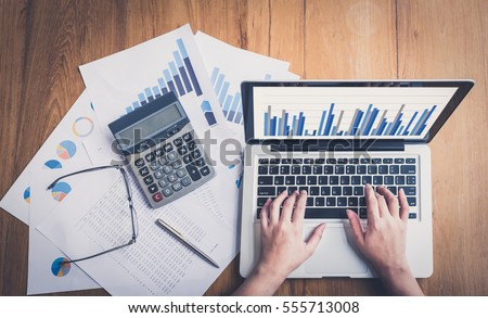 Accountants work analyzing financial reports on a laptop.