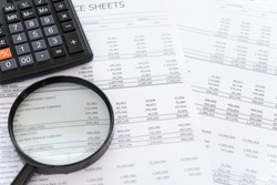 accounting audit concept. calculator and magnifying glass on financial statement and balance sheet annual.