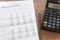 Accounting business concept. balance sheet report annual and calculator on accountant's desk.  above view.
