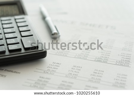 Accounting business concept. Calculator with accounting report and financial statement on desk.