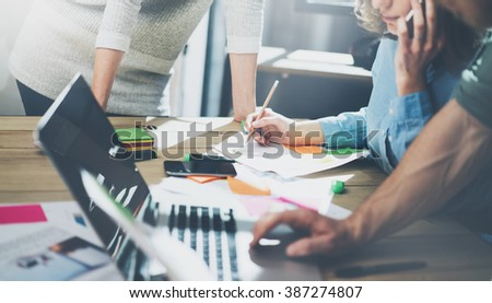 Accounting business meeting concept. Photo young businessman crew working with new startup project in modern loft. Generic design notebook on wood table, talking smartphone. Horizontal, film effect