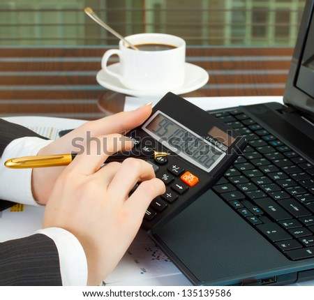 Accounting. Business woman at workplace with laptop and calculator - stock photo
