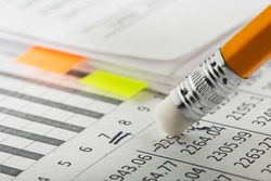 Accounting document with eraser erases blots in the document and checking financial chart. Concept of banking, financial report and financial audit.