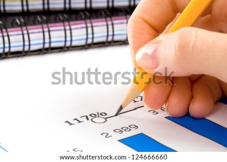 accounting. Female (woman) calculating and writing on chart