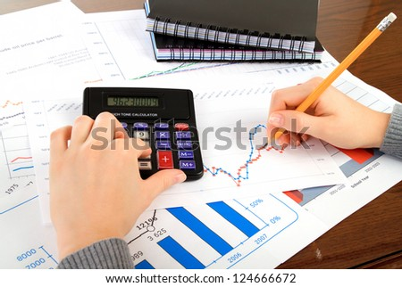 accounting. Female (woman) calculating and writing on diagram
