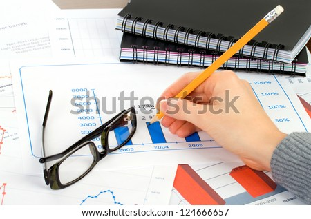 accounting. Female (woman) with black glasses calculating and writing on chart