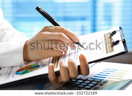 Accounting.Woman's hand with a pen writing on paper
