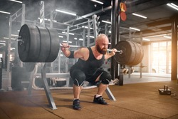 Acctive strong weightlifter sitting with heavy barbell in hands, squatting in modern gym room, professional sport concept, white smoke in the air, indoor side shot