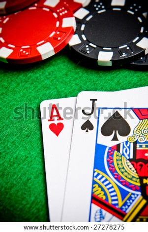 Ace of hearts and black jack with black and red poker chips.