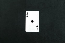 Ace of Spades playing card, black background.