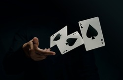 Ace Spade Playing Card. Player or Magician Throwing and Levitating Poker Card by Hand. Front View. Closeup and Dark Tone