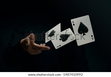 Ace Spade Playing Card. Player or Magician Throwing and Levitating Poker Card by Hand. Front View. Closeup and Dark Tone Zdjęcia stock ©