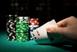 aces cards with white, red, blue, green and black chip son poker table green