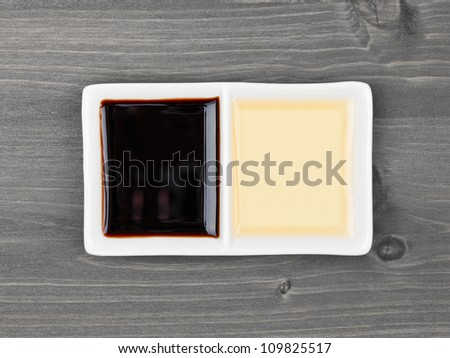 Aceto balsamico and Condimento bianco (light and dark balsamic vinegar) in bowl on wooden table