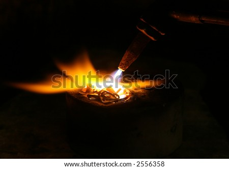 acetylene torch smelting hot precious metals, macro close up with copy space