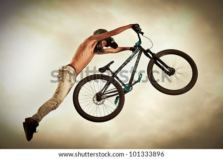 Achievement concept: Man flying high on a bike against the sky