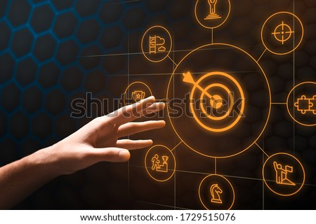 Achieving aims concept. Closeup of male hand reaching for virtual screen with target, arrow and business icons, collage