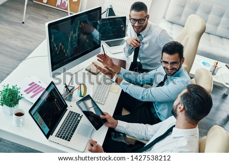 Achieving best results together. Top view of young modern men in formalwear analyzing stock market data and smiling while working in the office