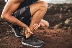 Achilles injury on running outdoors. Man holding Achilles tendon by hands close-up and suffering with pain. Sprain ligament or Achilles tendonitis.