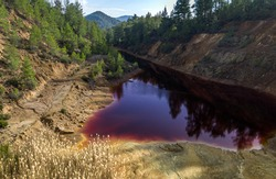 Acidic red lake in abandoned open pit mine in a forest, result of the pyrite ore extraction in the area
