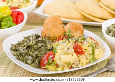 Ackee & Saltfish - Traditional Jamaican dish made of salt cod and ackee fruit. Served with callaloo and johnny cakes. Patties on background. #319688609
