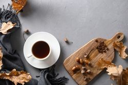 Acorn coffee with fall oak leaves and cozy scarf on gray concrete table. Coffee substitute without caffeine. View from above. Space for text.