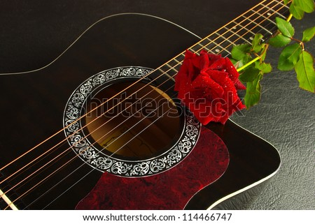 Acoustic black guitar and red rose against a textured background