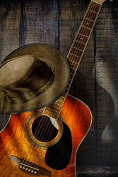 acoustic guitar and cowboy hat on wooden background