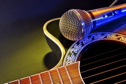 Acoustic guitar and microphone isolated with yellow and blue lights. Top view. Horizontal composition.
