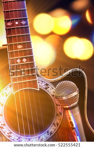 Acoustic guitar and microphone with lights in the background. Country or bluegrass concert concept. Front view. Horizontal composition. #522555421