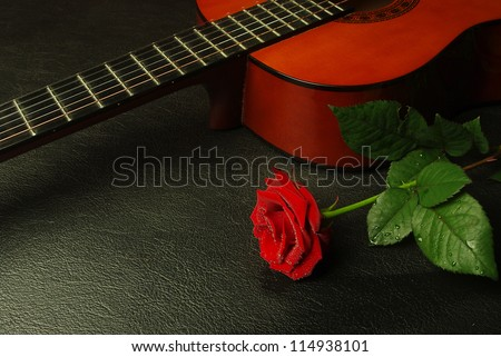 Acoustic  guitar and red rose against a textured background