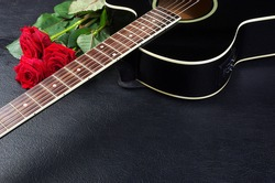Acoustic guitar and red roses