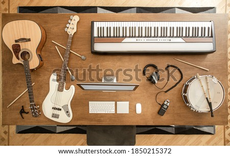 Acoustic guitar, bass guitar, snare drum, drum sticks, headphones, computer and musical keys on the background of a wooden table in a music studio top view. Photo stock ©