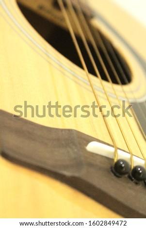 Acoustic guitar bridge pins and strings.